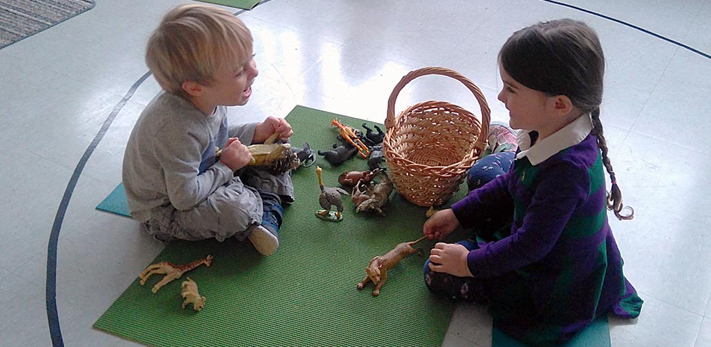 Montessori Casa students laugh and work together with African animals