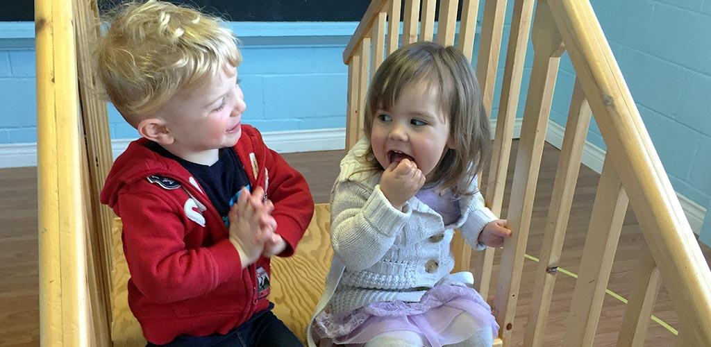 Two Montessori toddler students have fun on the toddler bridge